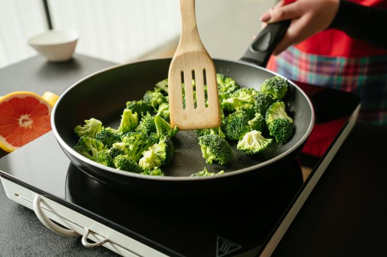 Tofu in padella, donna che mescola i broccoli in padella, fornello elettrico