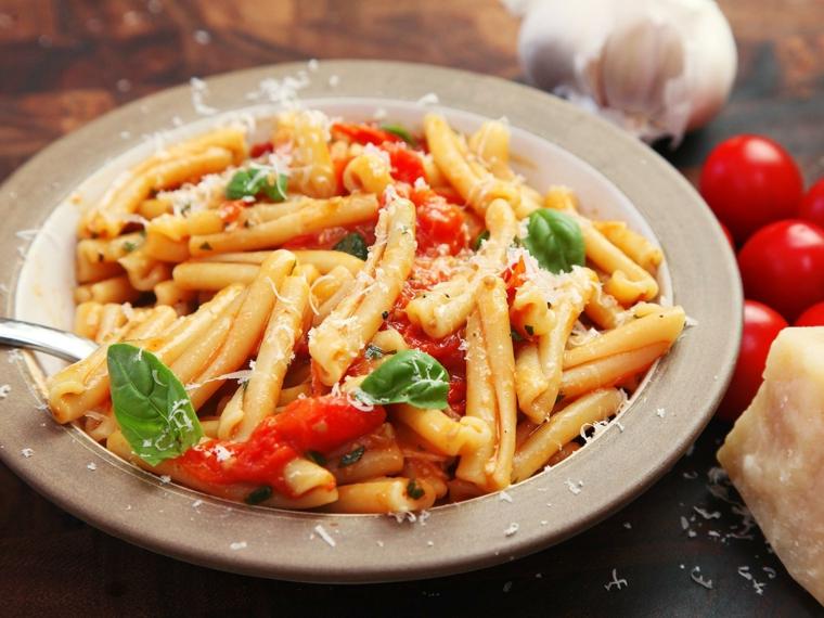 Ricette veloci estive per cena, pasta al pomodoro e basilico, parmigiano grattugiato in superficie