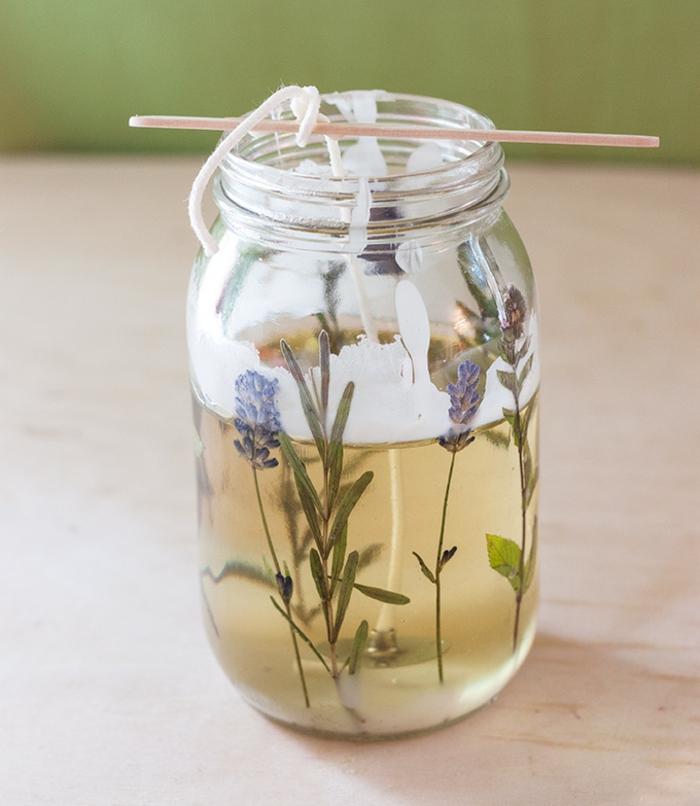 Candele fatte in casa, barattolo di vetro con cera sciolta e fiori di lavanda, stoppino con corda e bastoncino di legno