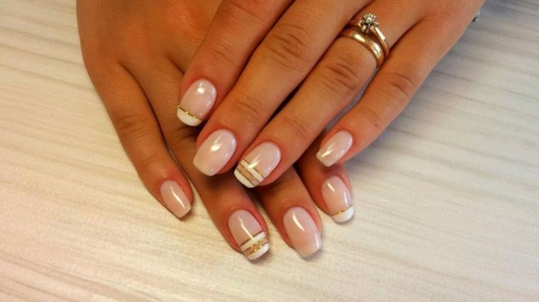 nail art creativa e chic, unghie color cipria con alcune decorazioni orizzontali bianche e oro