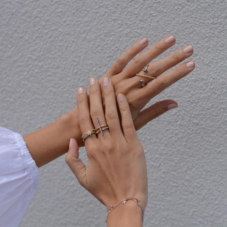 semplice e raffinata manicure con delle unghie neutre corte e squadrate e anelli di tendenza