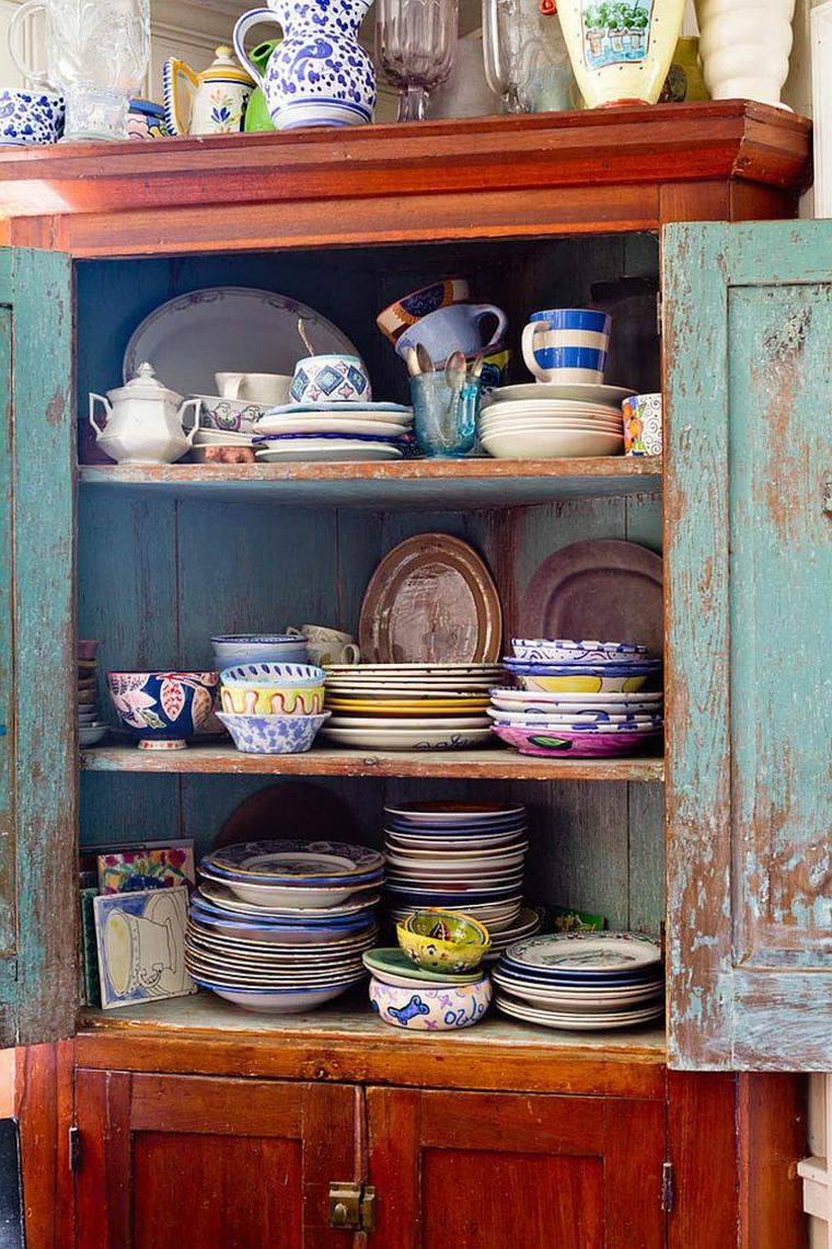 mobile in legno effetto anticato con all'interno piatti, ciotole e tazzine in ceramica colorata: idea stile shabby chic cucina