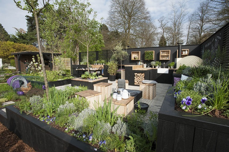Giardini idee da copiare, arredamento con una cucina da esterno e mobili in legno, tante piante sempreverdi e fiori