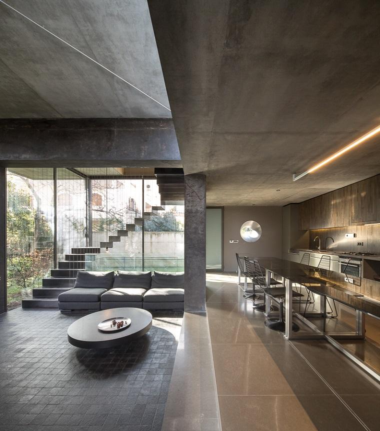 Soggiorno con divano grigio tre posti e tavolino rotondo, cucina a vista con un'illuminazione soffusa