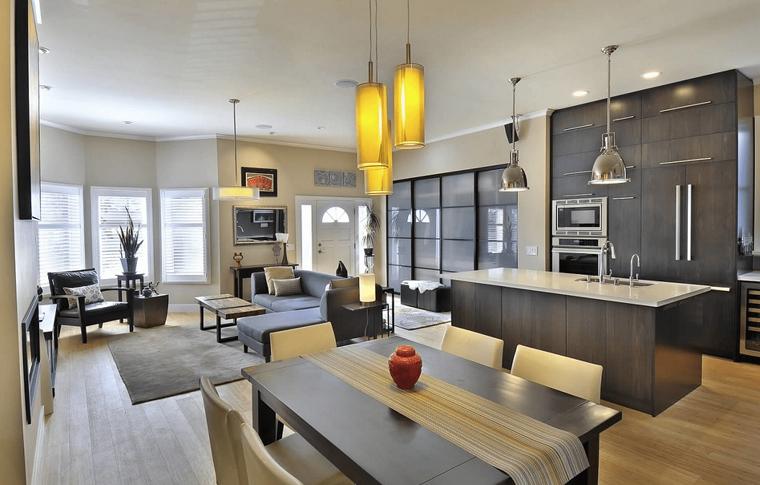 Arredamento cucina con isola centrale, lampadari a sospensione, pavimento in parquet colore chiaro