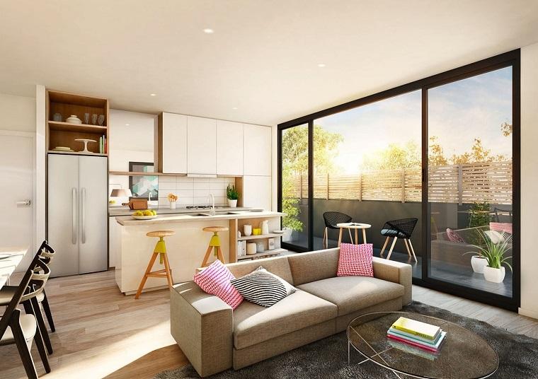 Esempi arredamento soggiorno, divano beige con cuscini colorati, tappeto grigio e tavolino di vetro