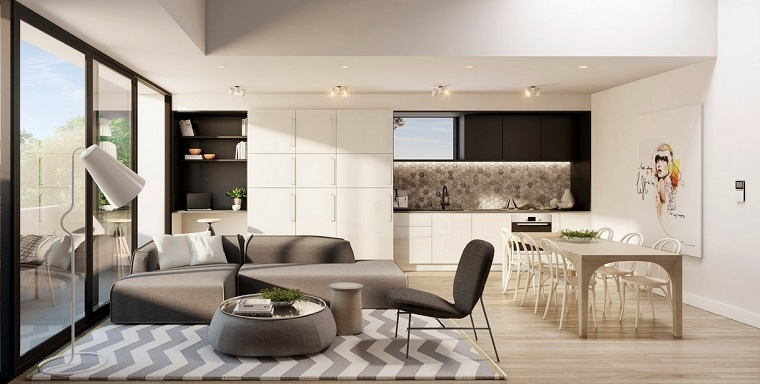 Cucina soggiorno ambiente unico, zona giorno con tappeto e un divano di colore grigio, tavolino rotondo con superficie di vetro