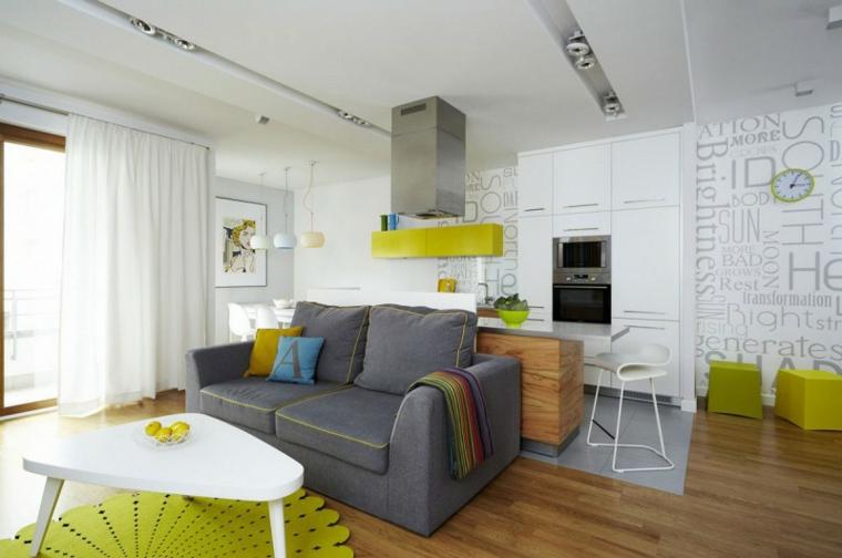 Arredare cucina soggiorno ambiente unico, divano di colore grigio, cappa sospesa sull'isola
