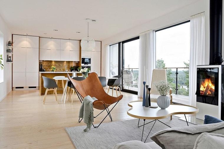 Soggiorno con divano e poltrona di legno, camino moderno, cucina open space moderna bianca
