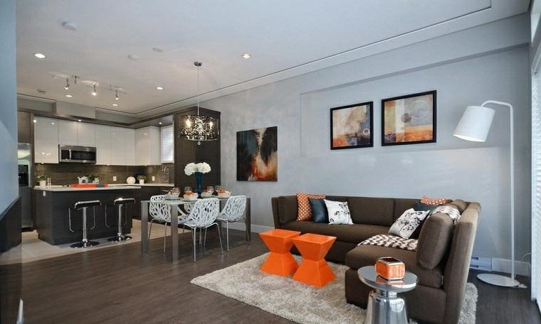 Cucina con isola, divano angolare, tavolini di colore arancione