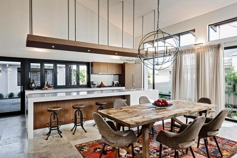 Ambiente aperto con cucina e sala da pranzo, tavolo di legno con sedie in tessuto