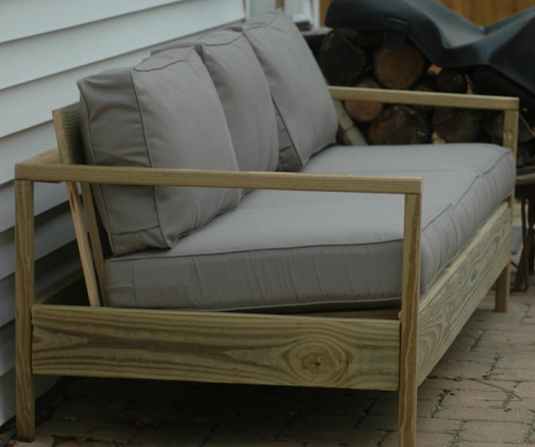 esterno con un divano pallet con dei cuscini grigi realizzato fai da te