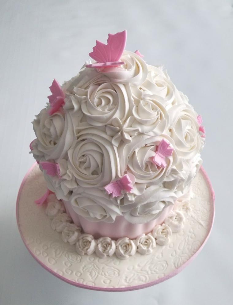 Torta di compleanno facile, decorata con panna montata bianca e decorata con farfalle rosa
