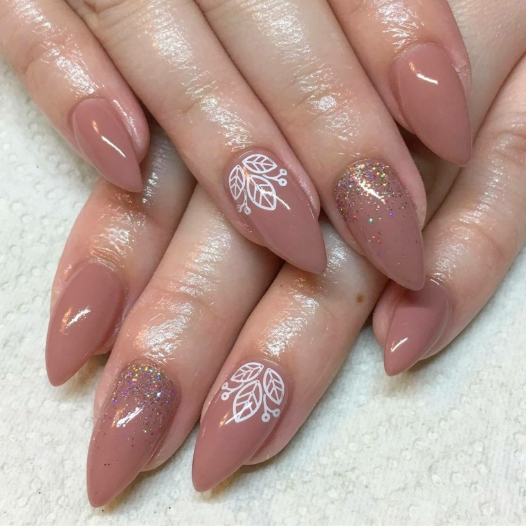proposta moda per unghie decorate color carne con motivi floreali bianchi e glitter multicolor