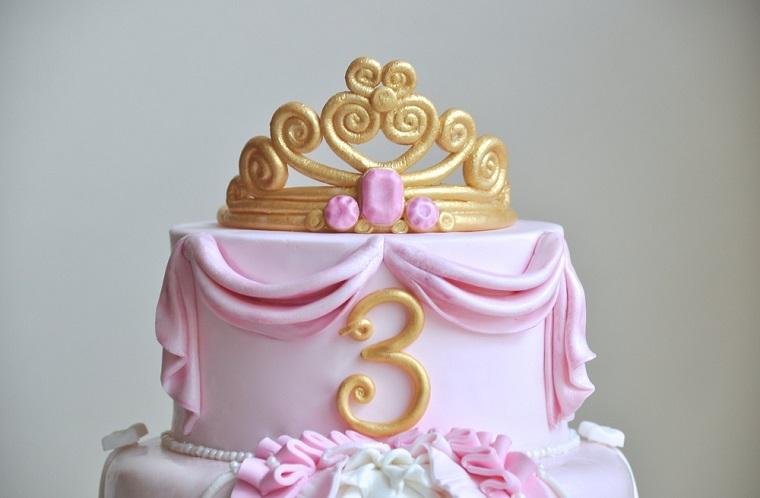 Torta compleanno bimba, dolce a due piani decorato con pasta di zucchero colore rosa e corona principessa