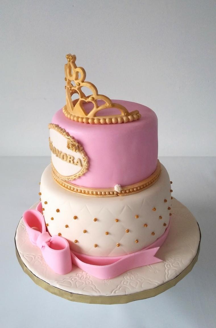 Torta compleanno bimba, decorata con corona in oro e fiocco rosa, scritta del nome in cornice