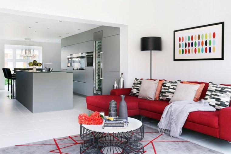 open space con divano angolare rosso, pareti bianche, tappeto grigio e rosso, cucina con isola grigia