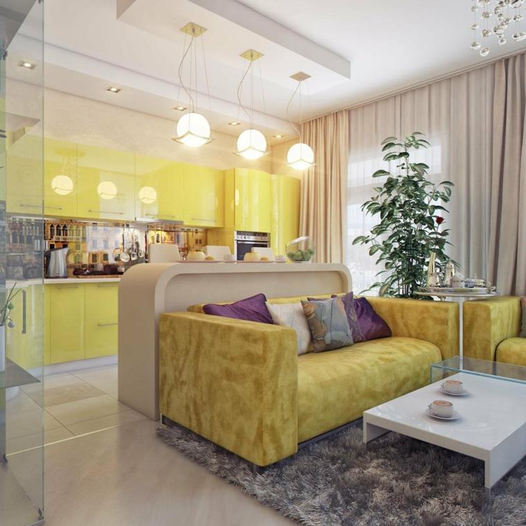 Divano di colore giallo, tavolino basso bianco, cucina con mobili gialli