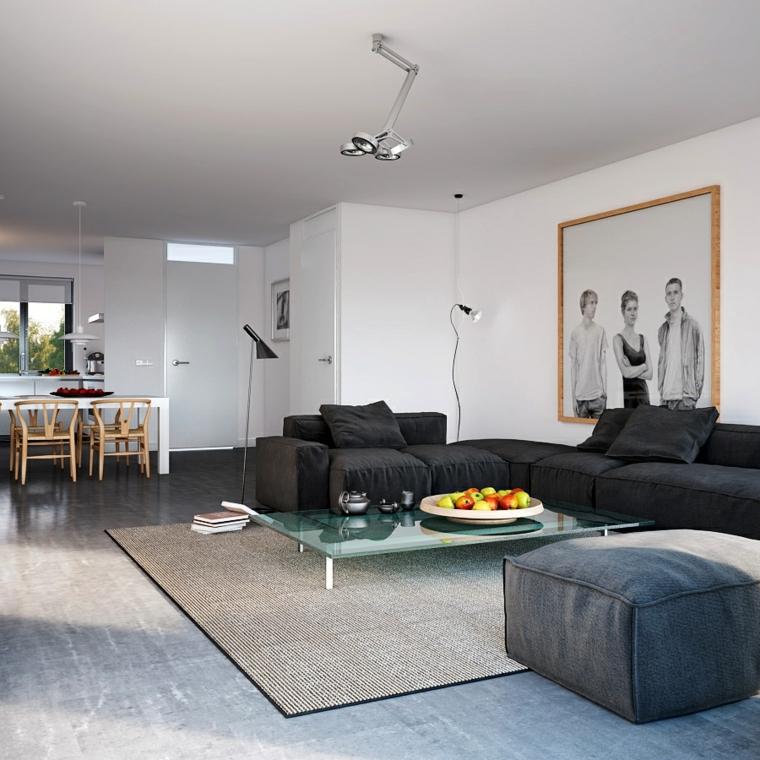 stanza open space con un grande divano angolare scuro, tavolo da caffè rettangolare in cristallo e tavolo bianco per il pranzo