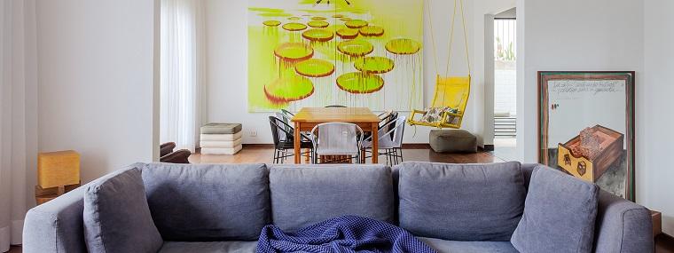 Esempi arredamento soggiorno, divano di colore grigio con cuscini, tavolo da pranzo in legno, decorazioni con quadri