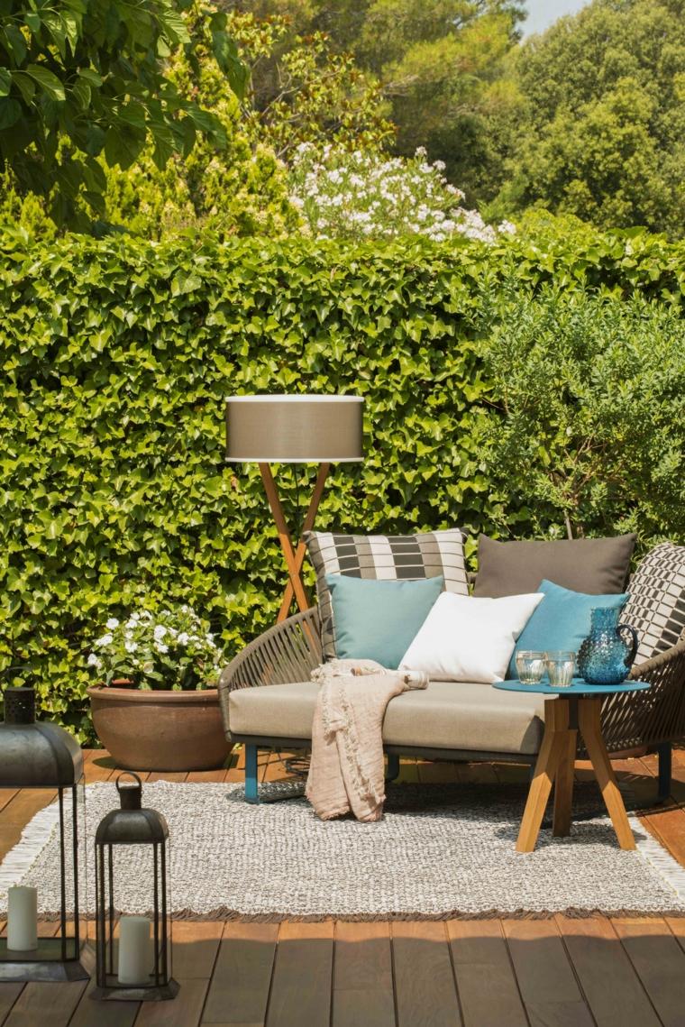 Arredamento da esterno con un divano e tappeto, decorazione con lanterne di metallo e siepe verde