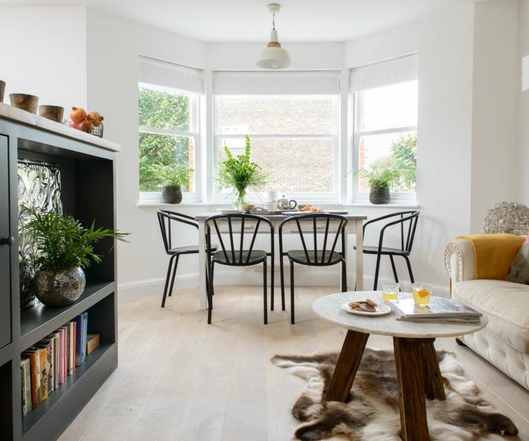 Salotto con tavolo da pranzo, mobile nero con libri, divano colore beige