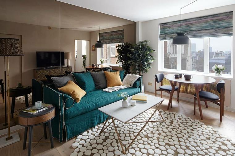 tavolo da pranzo tondo e un divano turchese con cuscini colorati, tende e lampade grigie, idea per soggiorni moderni