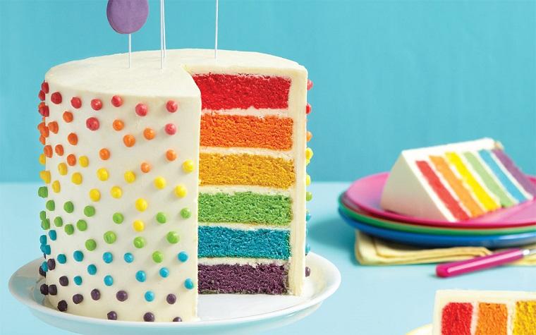 Torte di compleanno per bambini, idea con strati interni colorati arcobaleno e decorata con caramelle all'esterno