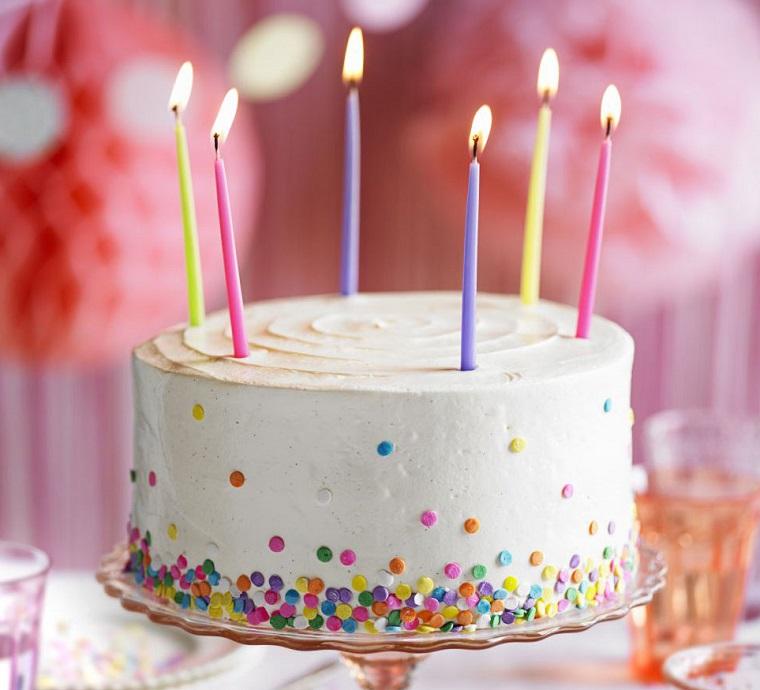 Torta rotonda rivestita con panna e caramelle, sei candeline colorate