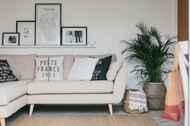 Divano di colore beige con cuscini colorati, cucina soggiorno open space, tappeto di canapa e pavimento in marmo