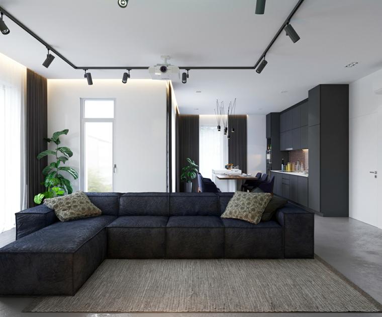 Cucina soggiorno ambiente unico, divano ad angolo nero, pavimento in gres colore grigio