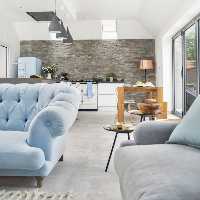 Cucina soggiorno ambiente unico, parete effetto pietra colore grigio, tavolo da pranzo in legno