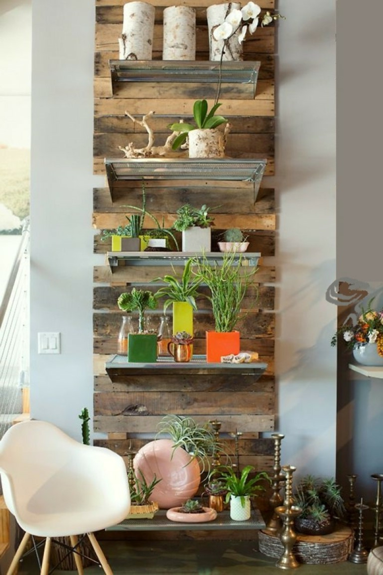 giardino verticale realizzato con le assi dei bancali, piante, candele, poltrona bianca