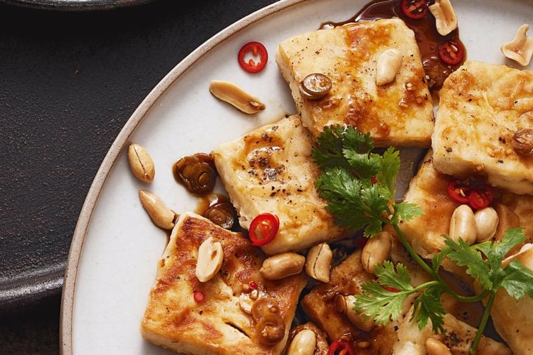 tofu tagliato a fette,dorato e condito con delle arachidi, peperoncino e coriandolo