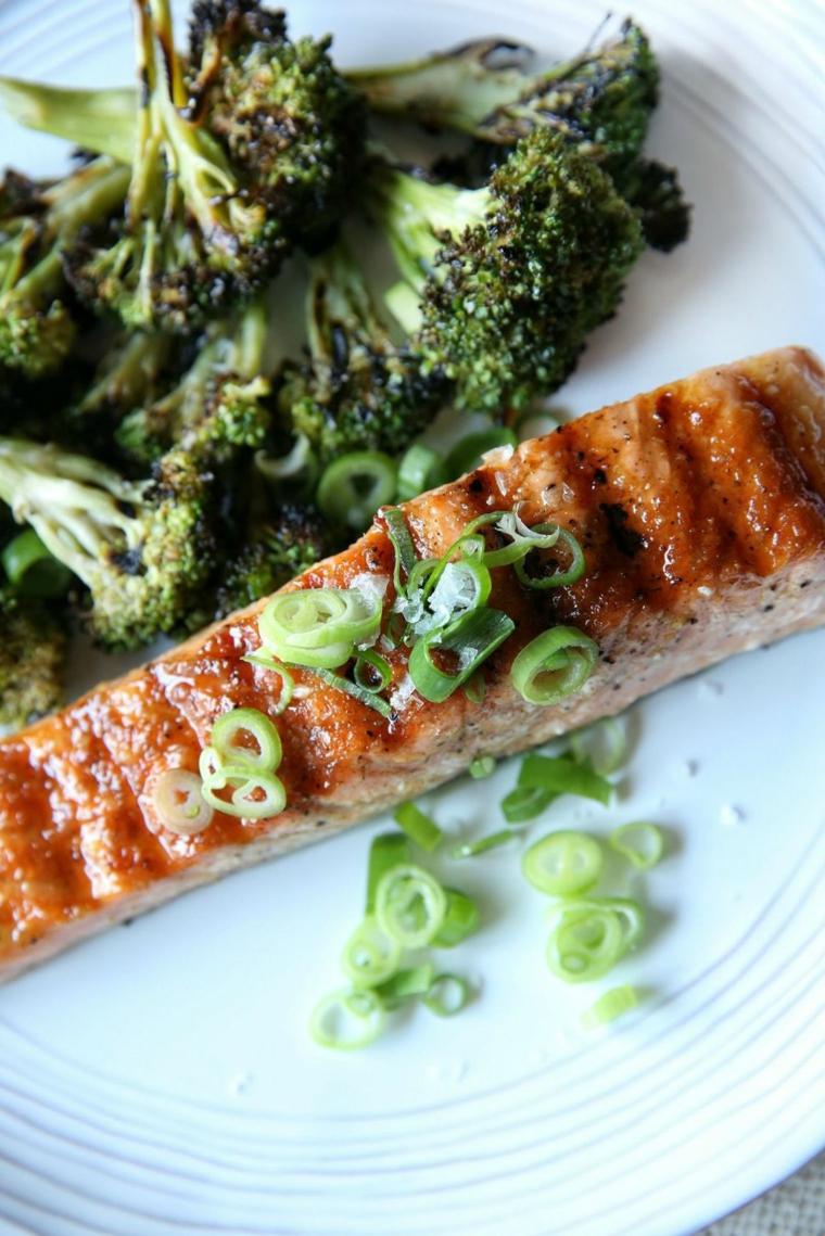 Broccoli grigliati come contorno al filetto di salmone, cena veloce, servita su un piatto bianco rotondo