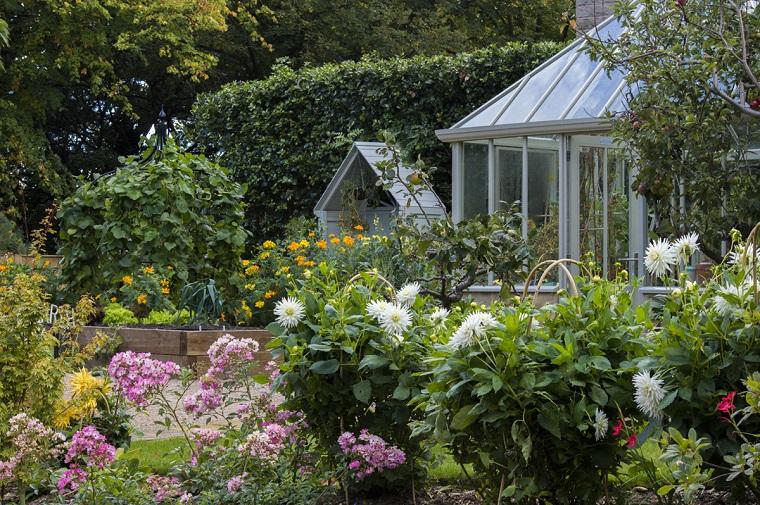 Idee per abbellire il giardino, una casetta di vetro e tanti fiori colorati, siepe e alberi alti