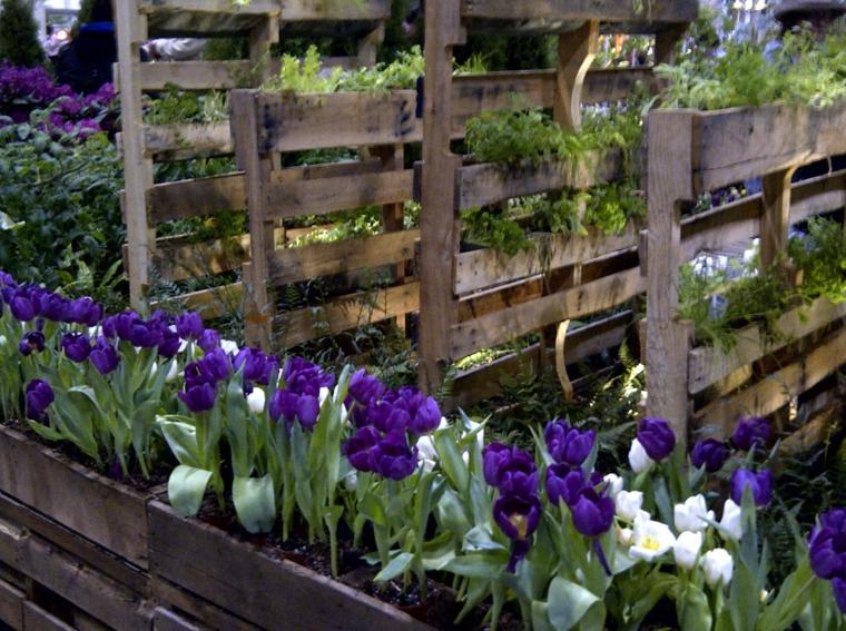 orto con dei fiori viola e bianchi e altre piante con divisori e vasi in pallet