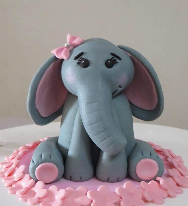 Torta con pasta di zucchero e un elefante, decorato con fiorellini rosa