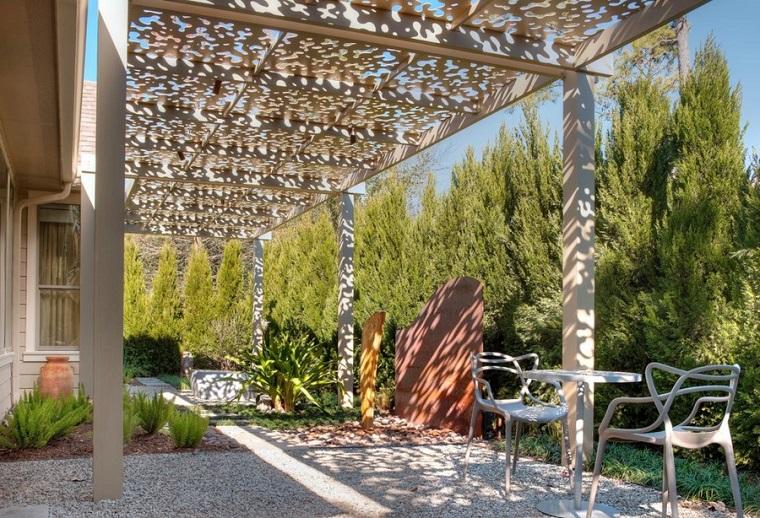 Piccoli giardino coperti da pergole in legno, pavimento con ghiaia e tavolo e due sedie