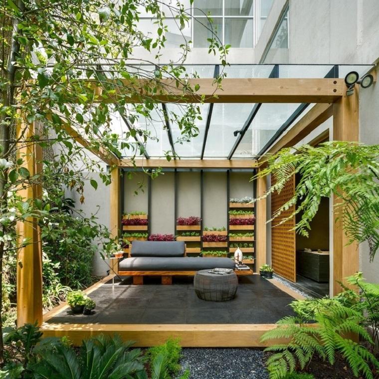 Arredo giardino con mobili in legno e una pergola, pavimentazione con ghiaia e piante tropicali