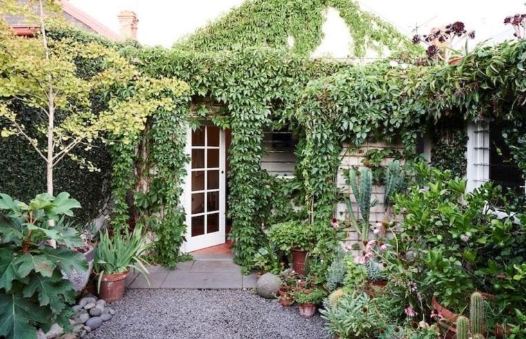 Idee per abbellire il giardino, piante rampicanti su tutti i muri della casetta, pavimento con ghiaia