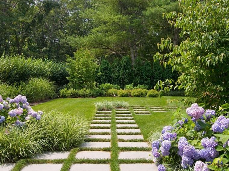 Idee per il giardino fai da te, camminamento con lastre di cemento e prato verde, fiori viola e alberi
