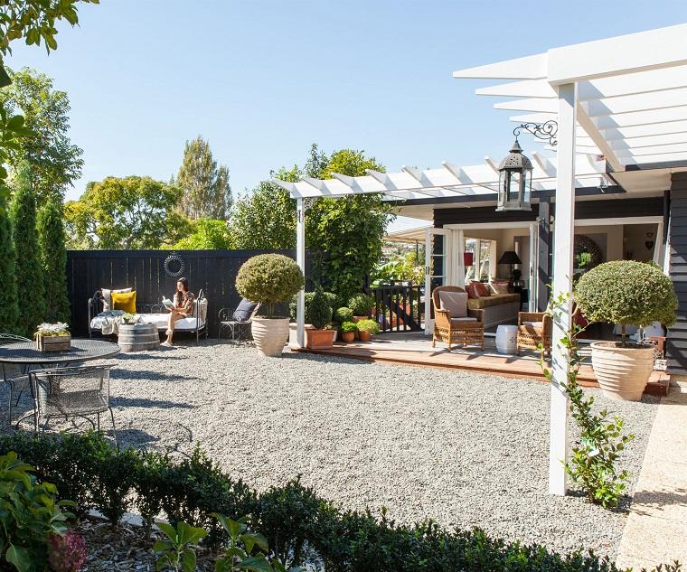 Arredo giardino, pergola di legno colore bianco, arredamento con mobili in ferro battuto e pavimento con ghiaia