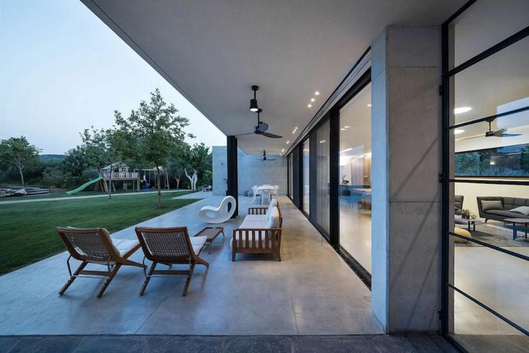 Una veranda con pavimento in marmo e mobili in legno, giardino con un prato verde