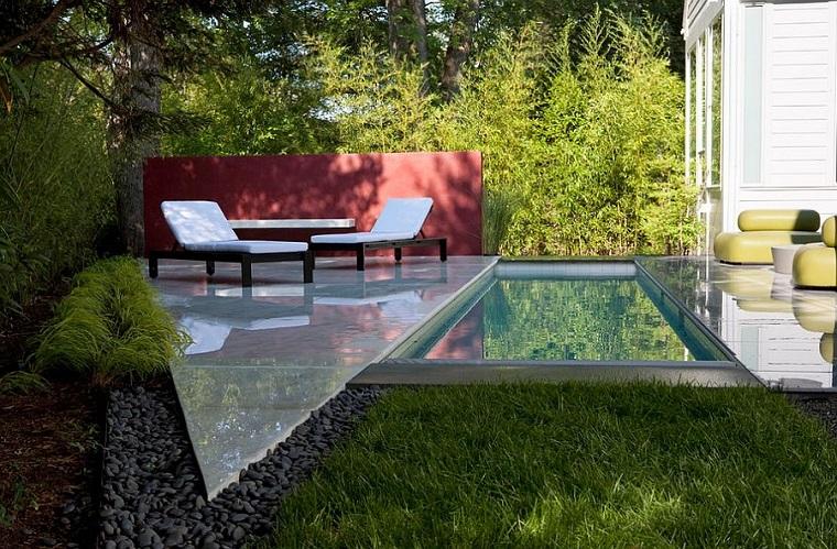 Piccoli giardino con piscina, arredamento con due sdrai e mobili in pelle di colore giallo