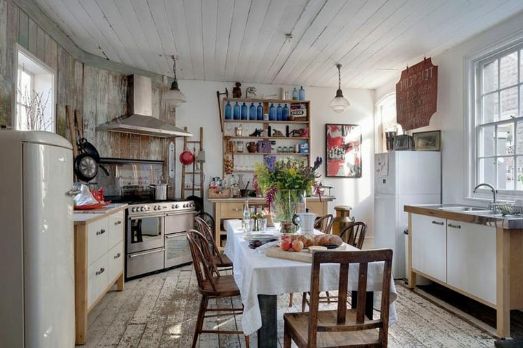 zona per il pranzo al centro della stanza, pavimento in legno dall'aspetto vissuto, cappa in acciaio: ambienti shabby chic