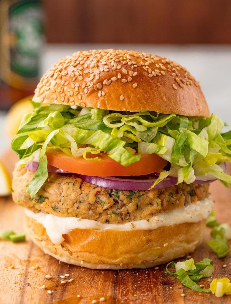 Burger al salmone, pane con sesamo e insalata verde, secondi piatti estivi, tagliere di legno