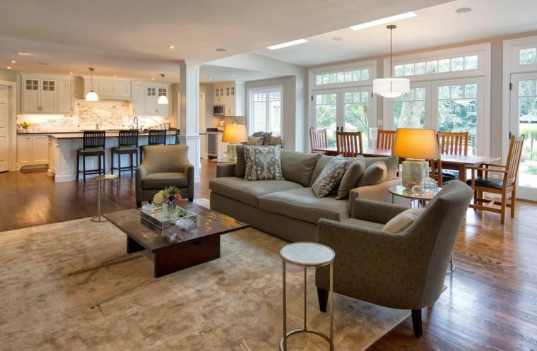 ampia stanza con cucina a vista, zona soggiorno e tavolo da pranzo, ampia vetrata e pavimento in parquet