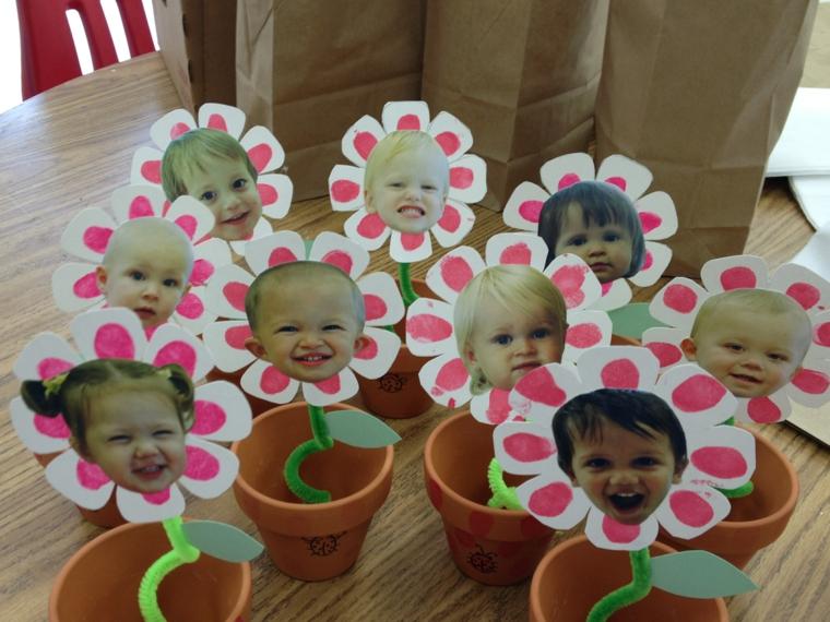originali vasetti di terracotta con all'interno dei fiori con la foro dei bimbi, lavoretti creativi festa della mamma