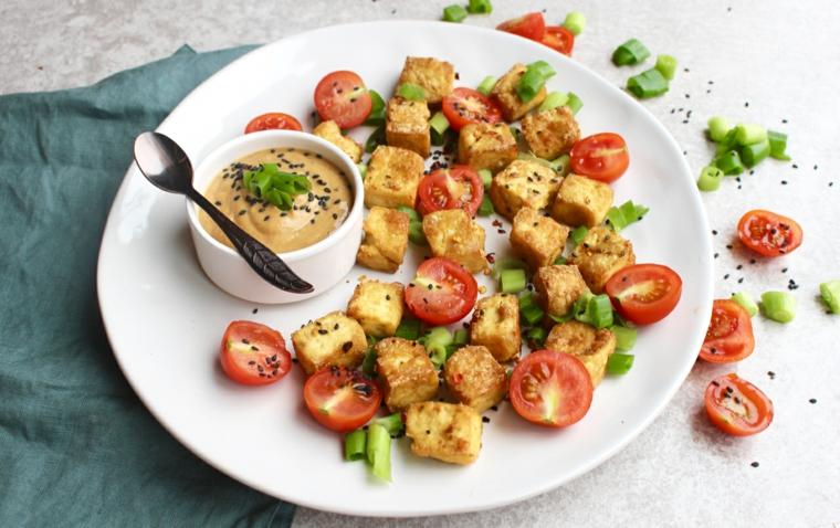 ricetta veloce da preparar con del tofu a cubetti, pomodori ciliegino e salsa di arachidi